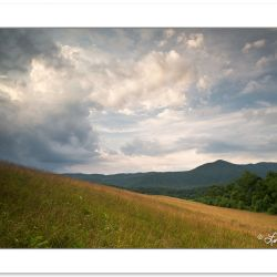 Storm clouds bubble up over a Cades Cove grassy meadow, Great Sm
